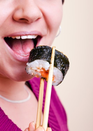close-up of young  woman with chopsticks and sushi photo
