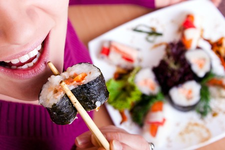 close-up of young  woman eating sushi  front view photo