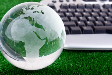 online learning: keyboard and glass globe on green grass Stock Photo