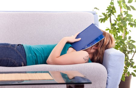 lying on couch: young girl fell a sleep while reading a book Stock Photo
