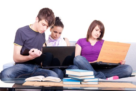 group of happy young students looking at laptop