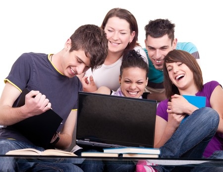 group of smiling teenagers looking at laptop Stock Photo