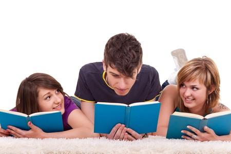 three teenagers reading  blue books on the floor photo