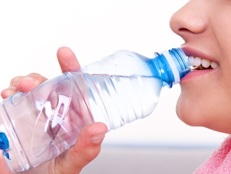 close-up of a female mouth drinking water from a bottle photo