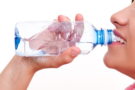 young woman drinking water from a bottle photo