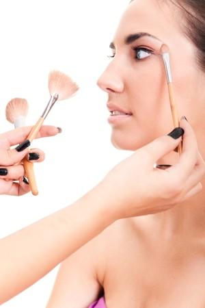 mujer maquillandose: primer plano de una mujer aplicar maquillaje aislado en blanco