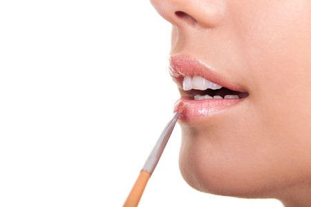 closeup of a woman applying lip gloss with brush Stock Photo - 7807589