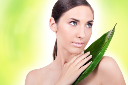 beautiful young woman posing with a leaf on green background photo