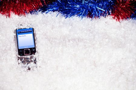mobile phone with message to Santa in snow photo