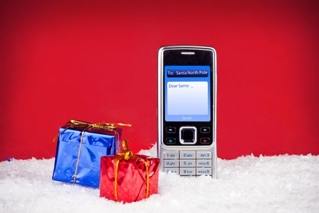 mobile phone with text Dear Santa on red Background photo