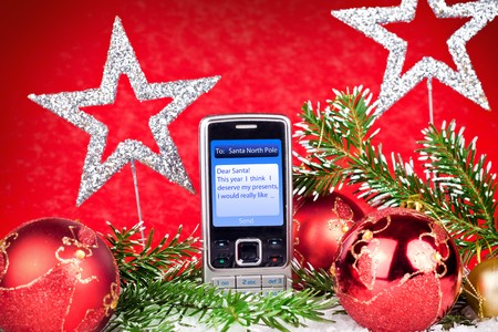 mobile phone with christmas message on red background photo