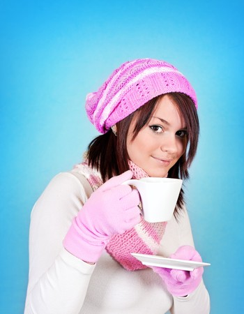 smiling winter  girl with tea on blue background photo