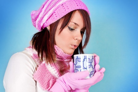 cute girl blows her tea on blue background photo