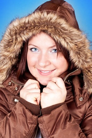 beautiful freezing girl in furry jacket on blue background photo