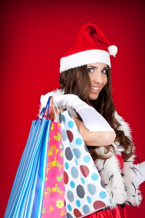 portrait of a happy santa woman with shopping bags photo