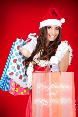 sexy santa woman holding colorful shopping bags photo