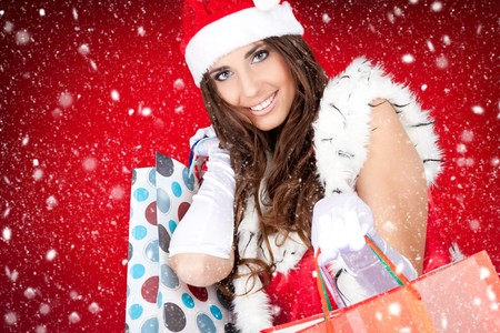 sexy santa woman holding colorful shopping bags while snowing photo