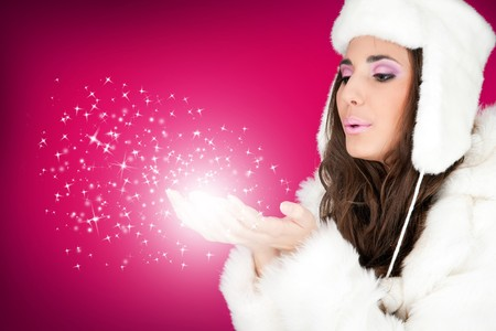 beautiful winter woman blowing snowflakes from her hands photo