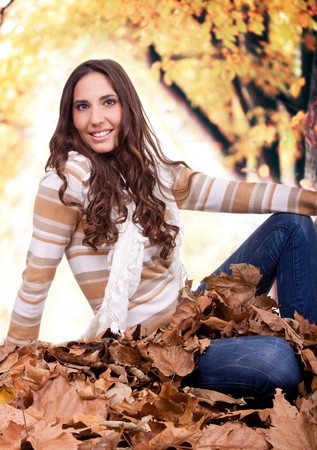 beautiful autumn woman sitting in a pile of dry leaves outdoor photo