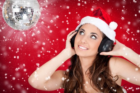 santas  helper: Christmas girl with disco ball listening music while snowing