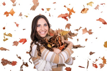 beautiful autumn woman holding a pile of leaves photo