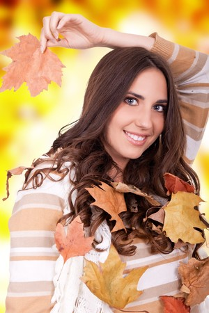 beautiful  woman with  dry leaves on orange background photo