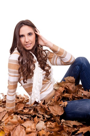 beautiful autumn woman sitting in a pile of dry leaves photo