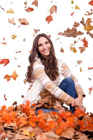 attractive autumn woman in a colorful pile of leaves photo