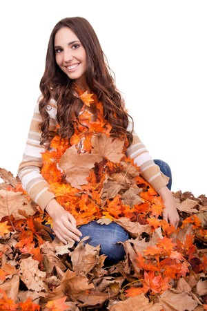 beautiful happy autumn woman covered with mapple leaves photo