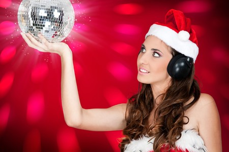 costume ball: sexy santa girl with disco ball listening music Stock Photo