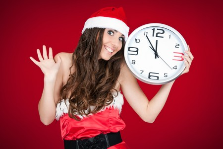 excited Christmas girl holding clock and pointing at time photo