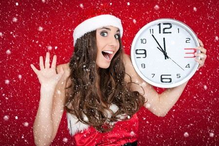 excited santa girl holding clock while snowing photo