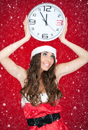 happy santa woman holding clock on red background photo