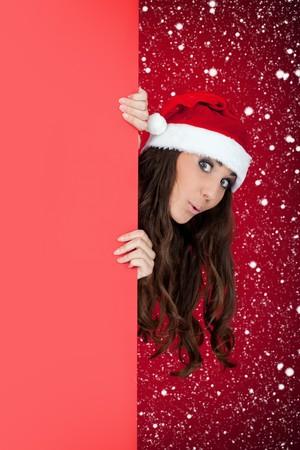 santas  helper: funny  santa girl peeping over blank billboard while snowing