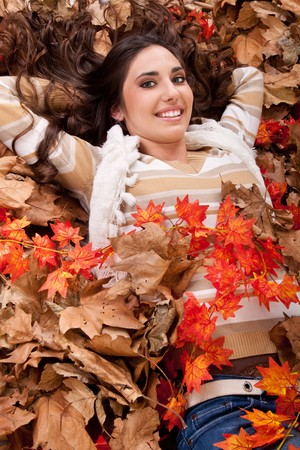 pretty brunette young woman in autumn leaves photo