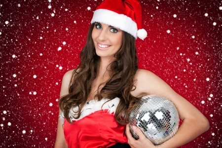 costume ball: brunette girl in santa costume holding disco ball  Stock Photo