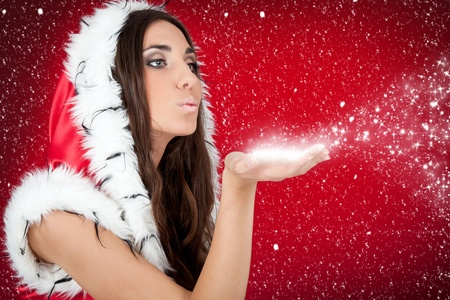 attractive woman in Christmas costume blowing snow form hand Stock Photo - 8431440