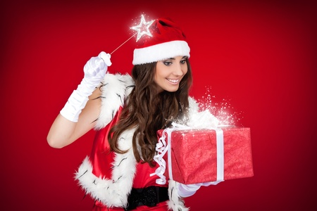 santa woman adding little magic to Christmas present photo
