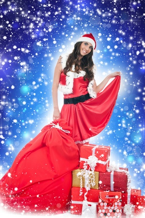 beautiful santa woman with presents on blue background photo