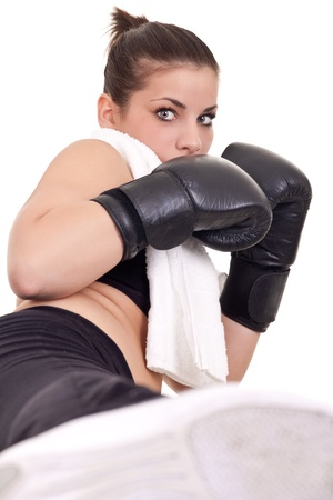 cute woman with boxing gloves giving  high kick  photo