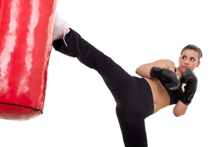 punching bag: young woman kick a punching bag- isolated on white Stock Photo