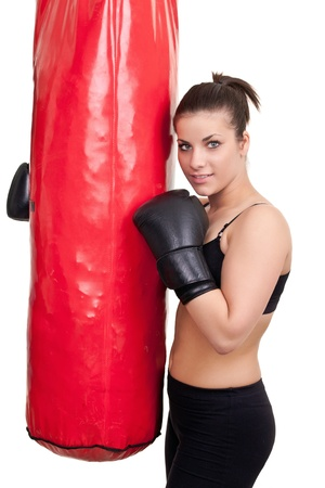 smiling girl after training with punching bag- isolated on white photo