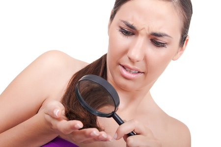 worried woman looking at her damaged hair -isolated on white  photo