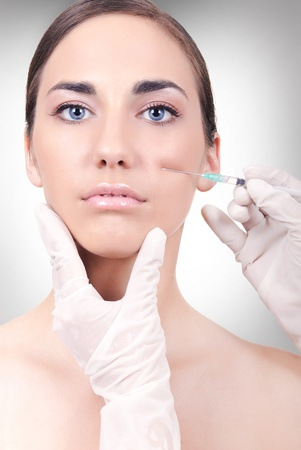 young woman having a collagen or botox injection on white background photo