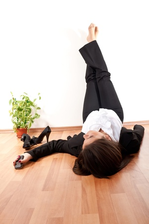 office shoes: businesswoman relaxing with her legs up  on wall at home