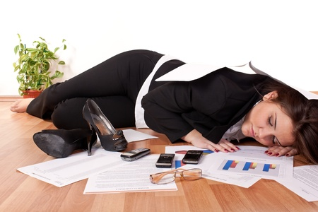 Tired overworked business woman sleeping on floor being exhausted from work