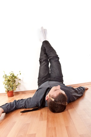 businessman relaxing with his legs up  on wall at home photo
