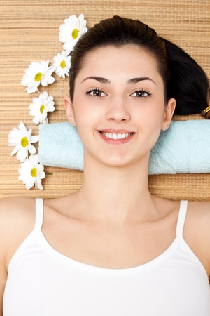 captivating young woman lying on a massage table with flowers in a spa center,view of the above