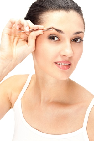 tweezers: close up, woman looking in mirror and plucking eyebrows, isolated on white Stock Photo