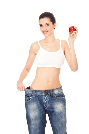 woman in big jeans holding apple, isolated on white background Stock Photo - 9129268